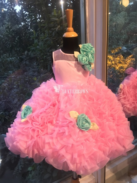 A frilly pink puffy flower girl dress with mint and white flowers
