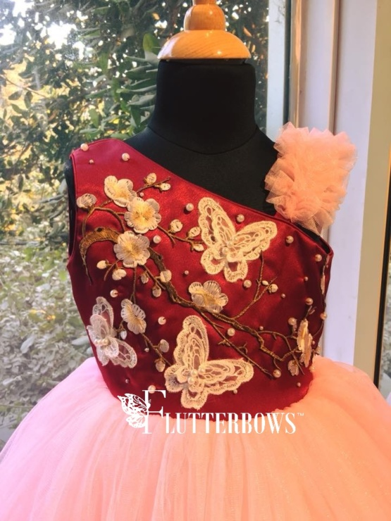 A maroon body with pink fluffy base with butterflies, flowers and pearls dress for baby girl