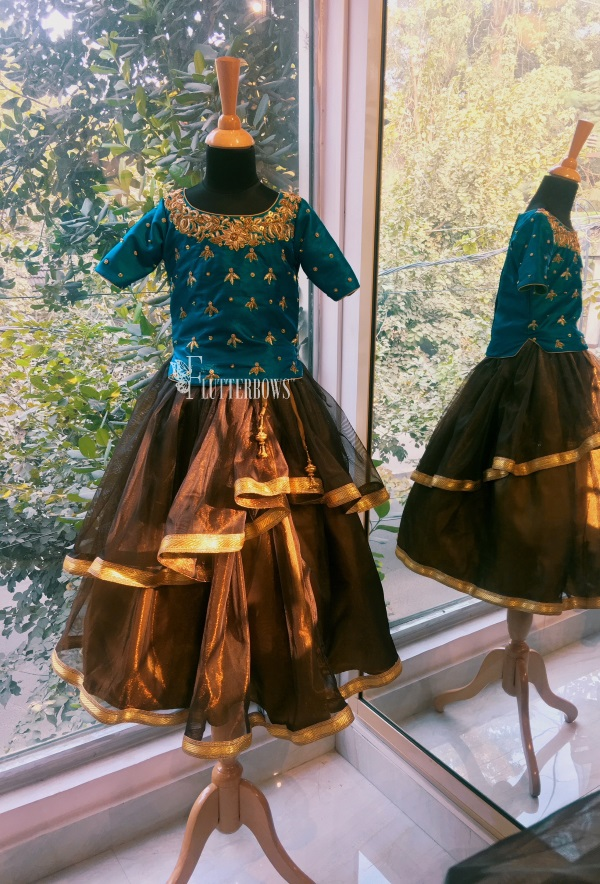 A blue green handwork zari blouse with a rustic brown skirt for girls